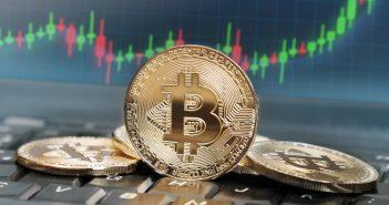 Bitcoins auf einer Tastatur vor einem Preischart